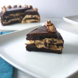 Flourless Chocolate Cake filled with White Chocolate Peanut Butter Cream covered in chocolate ganache topped with peanut butter cups