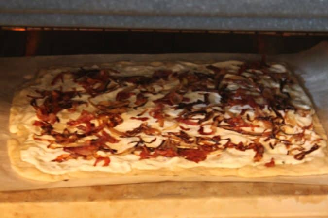 Flammkuchen is a German thin crust pizza with crispy bacon and onions with a sour cream/greek yogurt sauce.